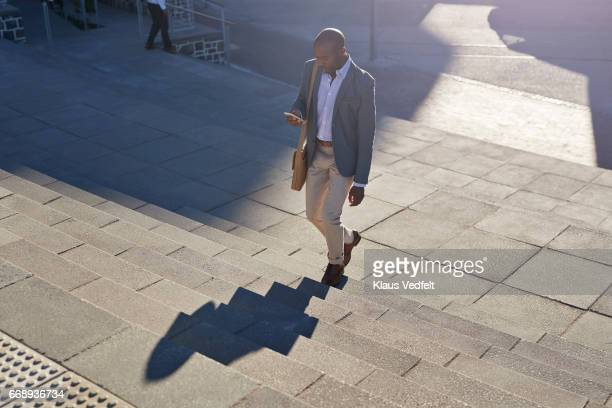 Businessman looking at phone, while walking on staircase