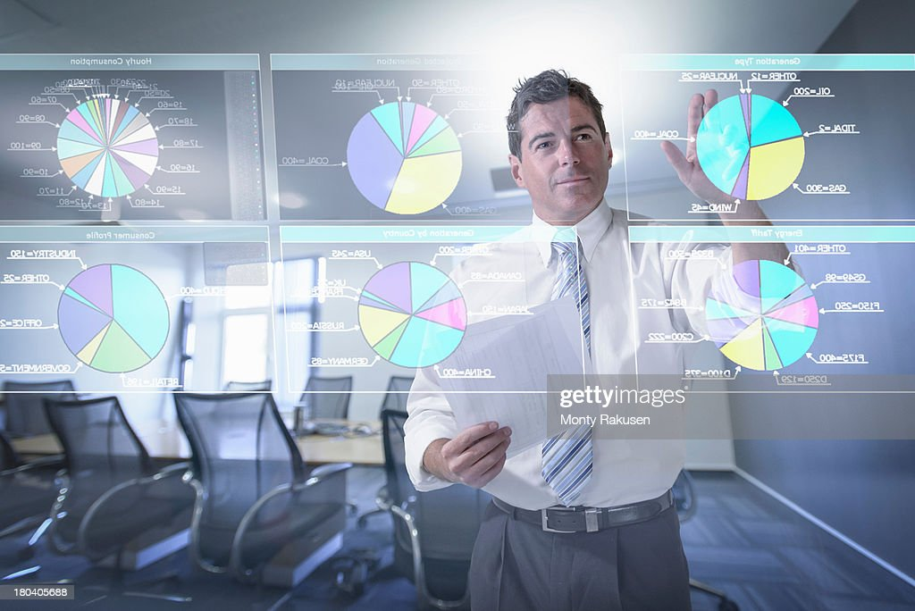 Businessman looking at pie charts on interactive screen : Stock Photo