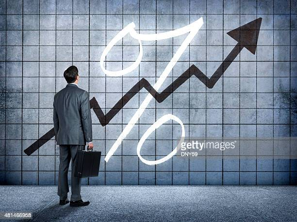businessman looking at prospect of higher interest rates - percentage sign stock pictures, royalty-free photos & images