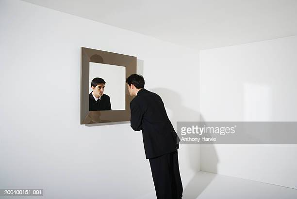 businessman looking at reflection in mirror on wall - solo un uomo foto e immagini stock