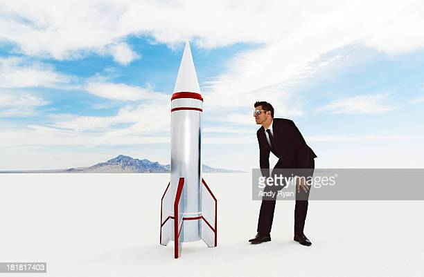 Businessman looking at rocket in desert.