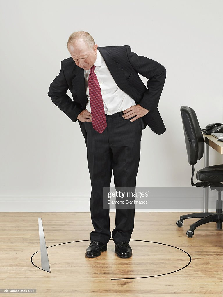 Businessman looking at saw cutting floor around it : Stock Photo