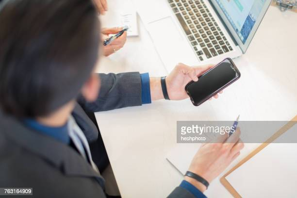 businessman looking at smartphone at desk - heshphoto stock pictures, royalty-free photos & images