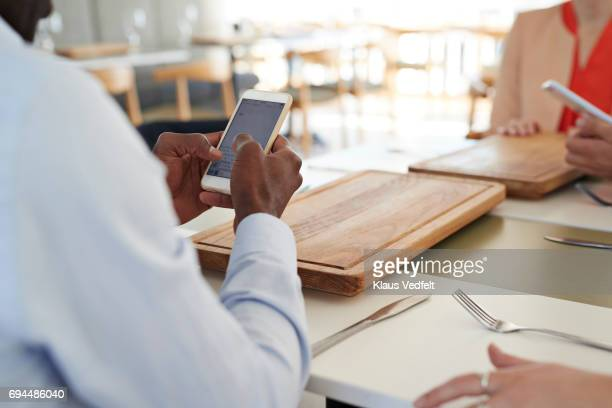 Businessman looking at smartphone, at lunch restaurant