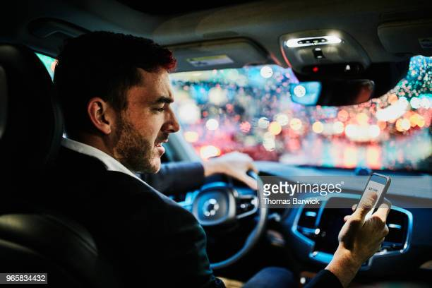 Businessman looking at smartphone in car before departing on evening commute