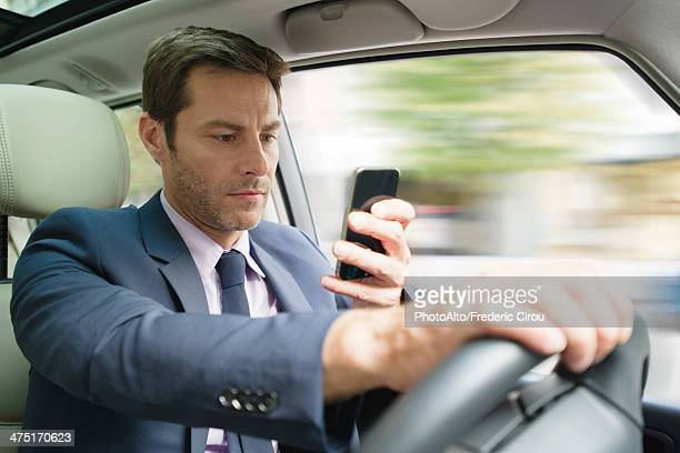 Businessman looking at smartphone in car