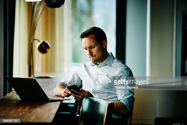 businessman looking at smartphone in office - biting lip stock pictures, royalty-free photos & images