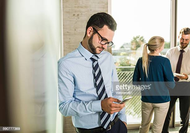 Businessman looking at smartphone with colleagues in background