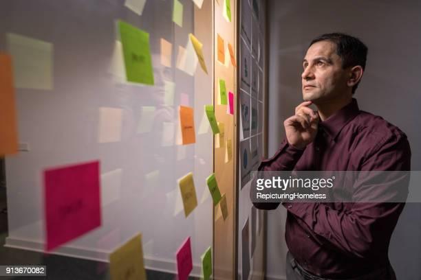 ein geschäftsmann ist tief in gedanken versunken, währrend er auf notizzettel schaut - repicturing homeless stock-fotos und bilder