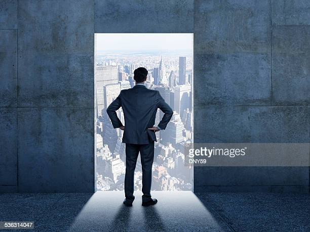Businessman Looking At The Big City From Inside Industrial Building
