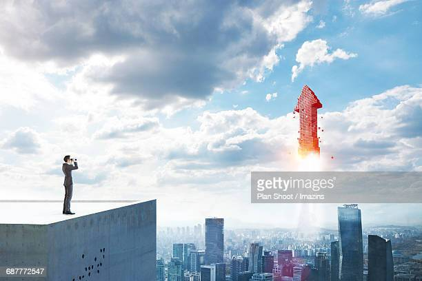 A businessman looking at the rising arrow above the city through the telescopes