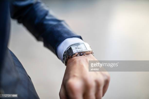businessman looking at this watch - wrist stock pictures, royalty-free photos & images
