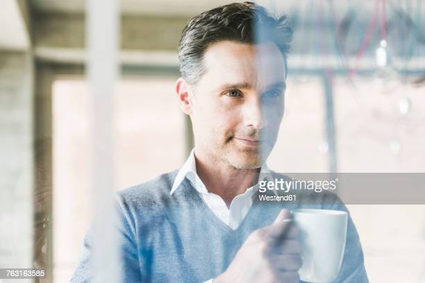 businessman looking at transparant projection screen in office - kaffee getränk stock-fotos und bilder