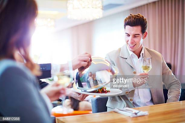 Businessman looking at waiter lifting serving dome in hotel restaurant