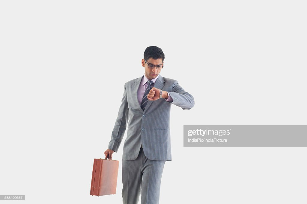 Businessman looking at watch : Stock Photo