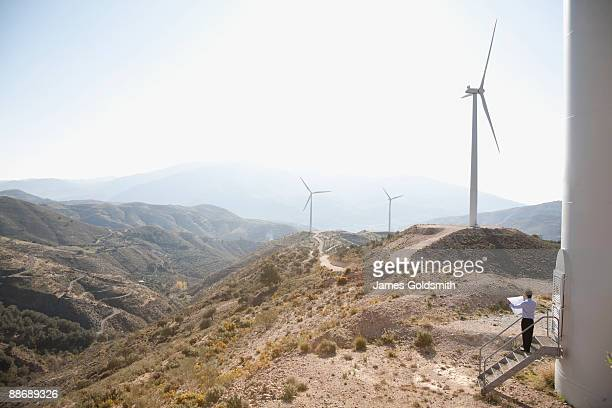Businessman looking at wind turbines in remote area
