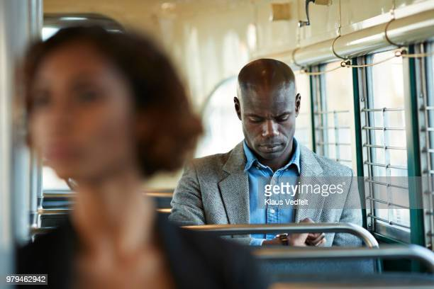 Businessman looking at wristwatch while riding in San Francisco tram
