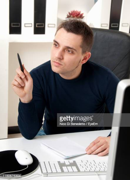 businessman looking away at desk in office - benedetto photos et images de collection