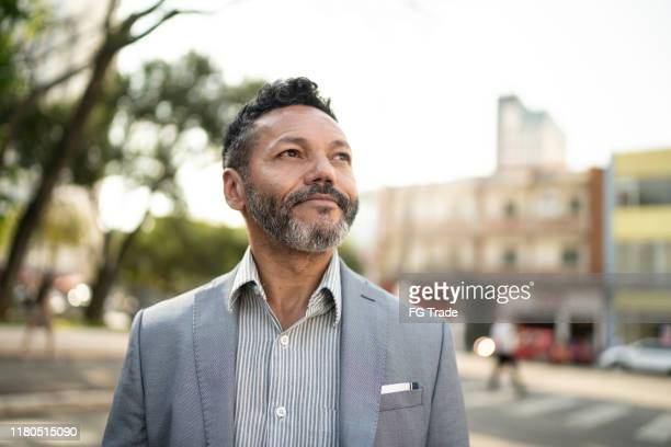 businessman looking away on the street - speranza foto e immagini stock