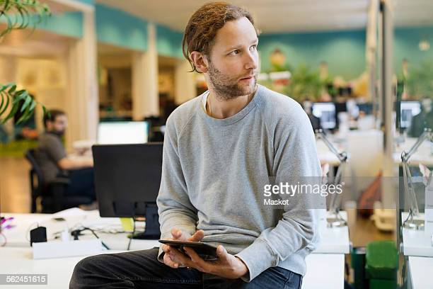 Businessman looking away while holding digital tablet on desk in creative office