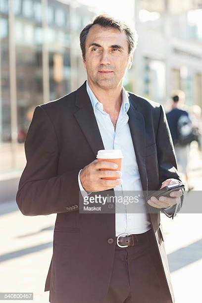 Businessman looking away while holding mobile phone and disposable coffee cup on city street