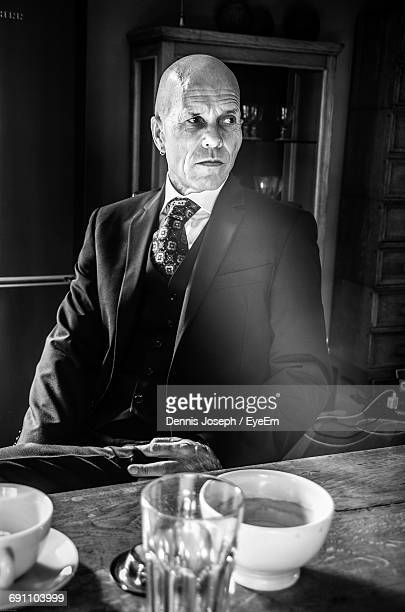 Businessman Looking Away While Sitting By Table