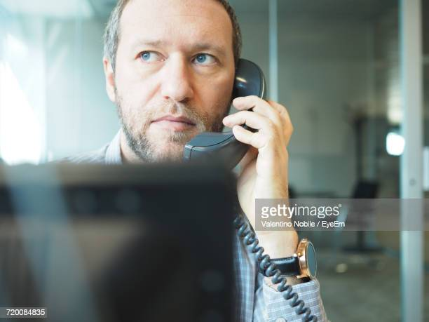 Businessman Looking Away While Talking On Landline Phone At Office