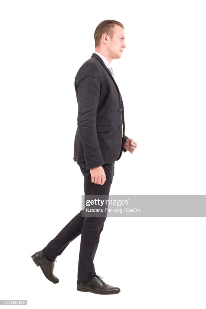 Businessman Looking Away While Walking By White Background : Stock-Foto