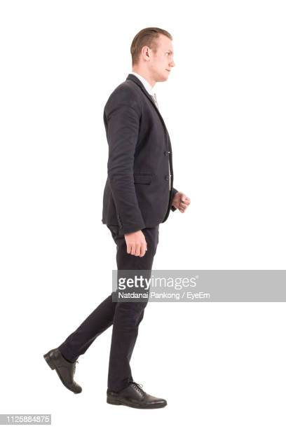 businessman looking away while walking by white background - van de zijkant stockfoto's en -beelden