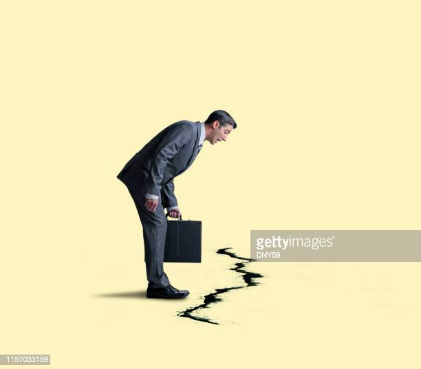 businessman looking down at a large crack in ground - bending over stock pictures, royalty-free photos & images