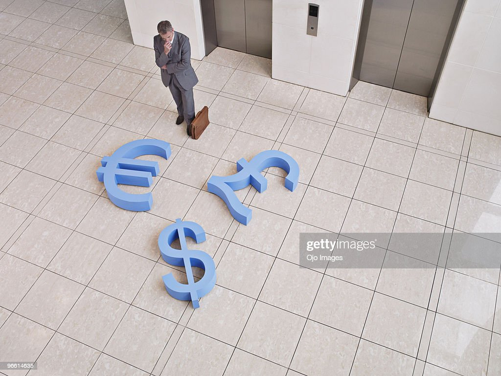 Businessman Looking Down At Dollar Euro And British Pound Symbols On