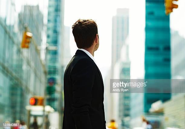 Businessman looking down city street, rear view.