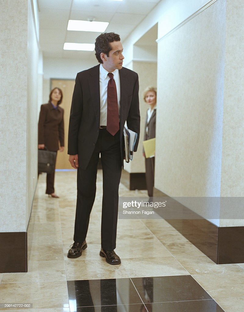 Businessman looking down corridor, colleagues in background : ストックフォト