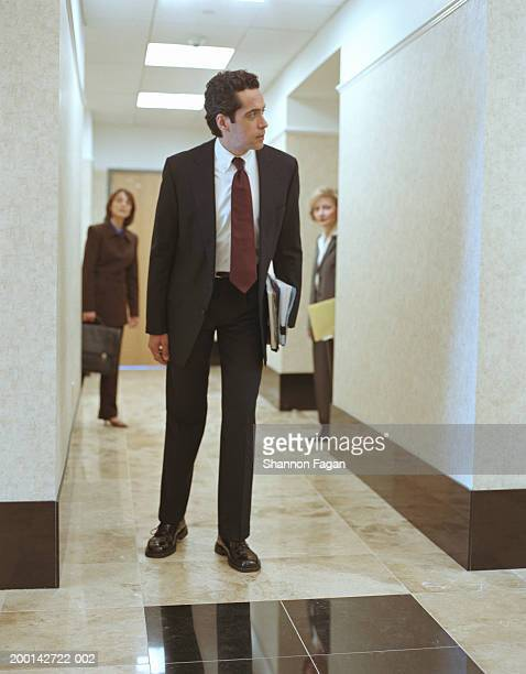 Businessman looking down corridor, colleagues in background