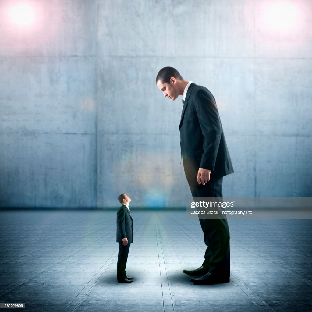 Businessman looking down on miniature colleague : Stock Photo