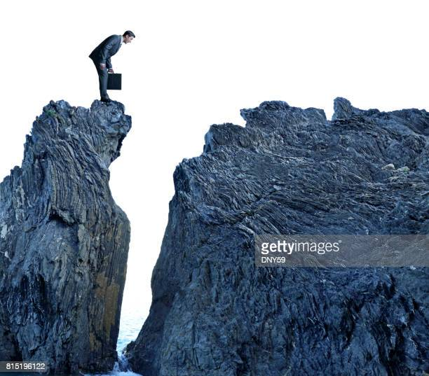 Businessman Looking Down On Top Of Rocky Cliff Above Ocean