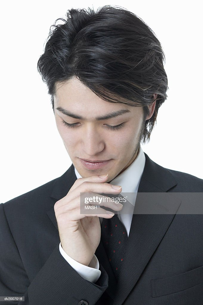 Businessman Looking Down With His Hand on His Chin : Stock Photo