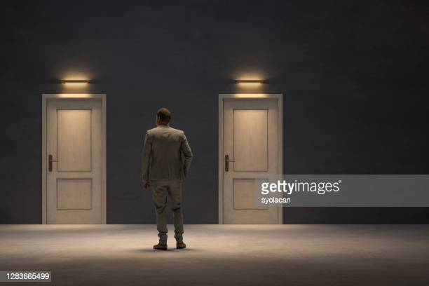 businessman looking for the right door to exit - syolacan stock pictures, royalty-free photos & images