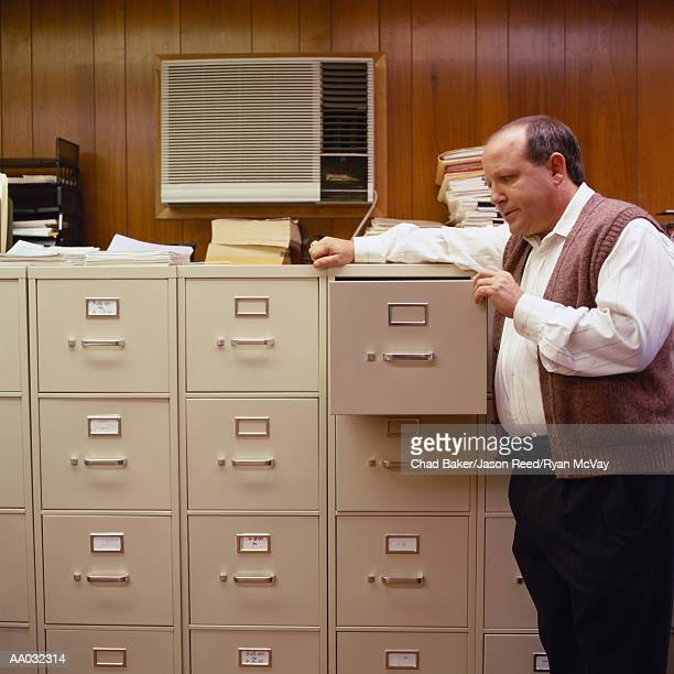 Businessman Looking in a Filing Cabinet