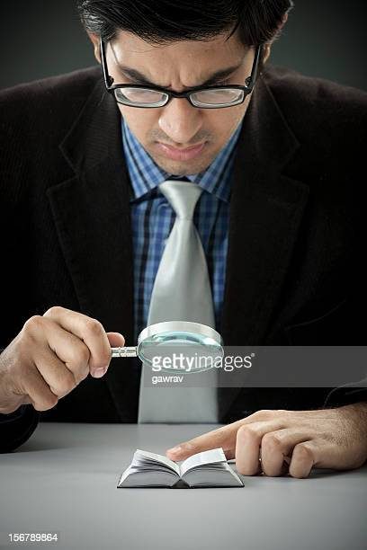 Businessman looking in a miniature book through magnifying glass