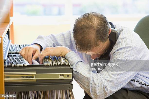 Businessman Looking in Filing Cabinet While Using Telephone