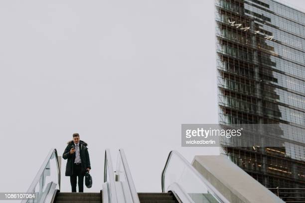 businessman looking in his smart phone driving on an escalator - erwachsener über 40 stock pictures, royalty-free photos & images