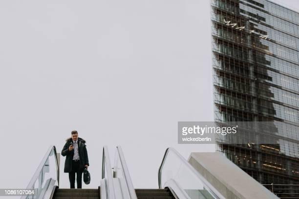 エスカレーター運転彼のスマート フォンで見ているビジネスマン - geschäftsmann ストックフォトと画像