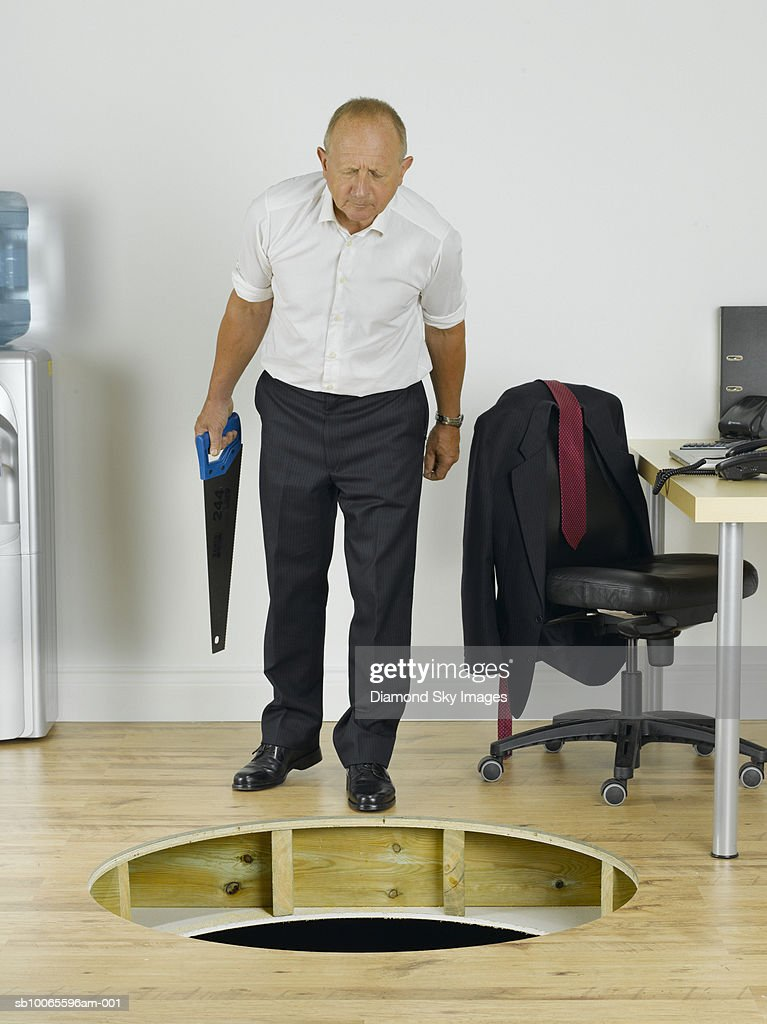 Businessman looking in to hole in wooden floor : Stock Photo