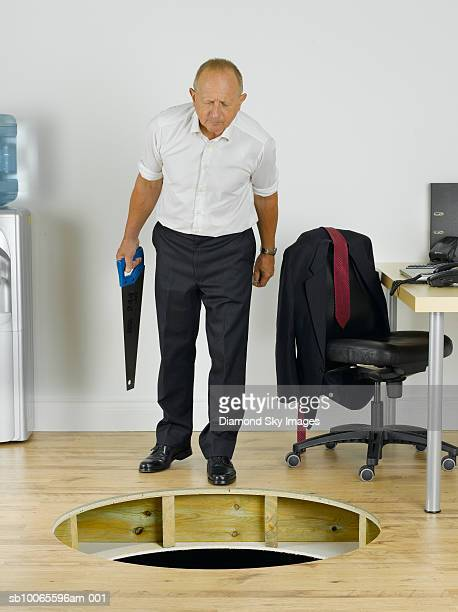 Businessman looking in to hole in wooden floor
