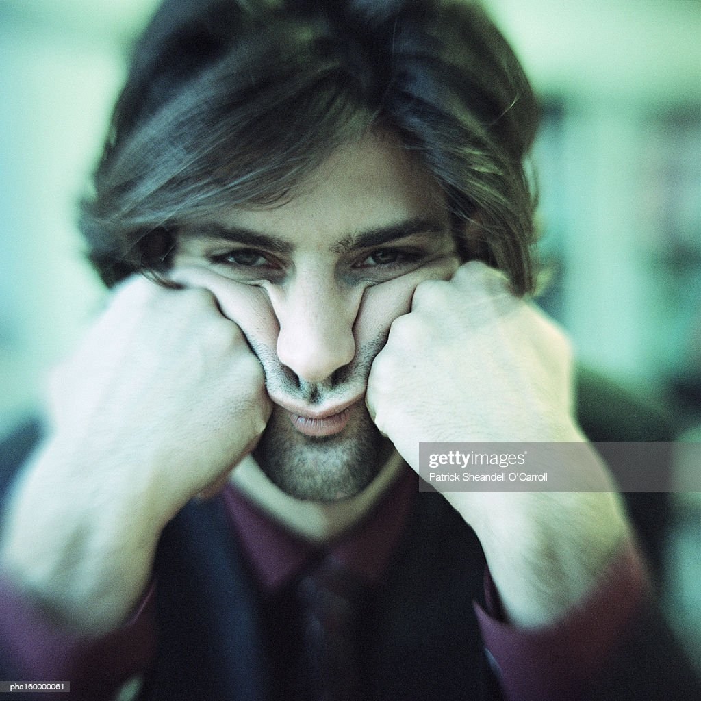 Businessman looking into camera, head in hands, portrait. : Stockfoto