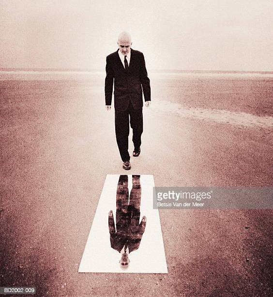 Businessman looking into full length mirror on beach (toned B&W)