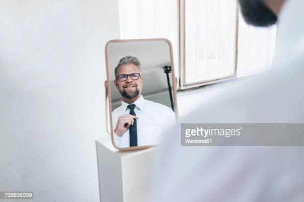 Businessman looking into mirror, fastening his tie