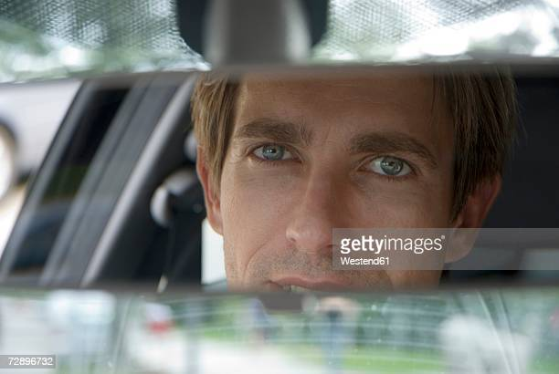 Businessman looking into rear view mirror, close-up