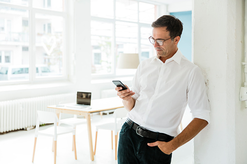Businessman looking on cell phone in bright office - gettyimageskorea